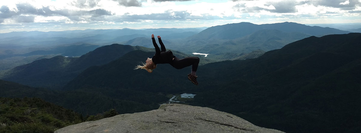 A student is suspended in the air mid-backflip with mountains and sky in the background