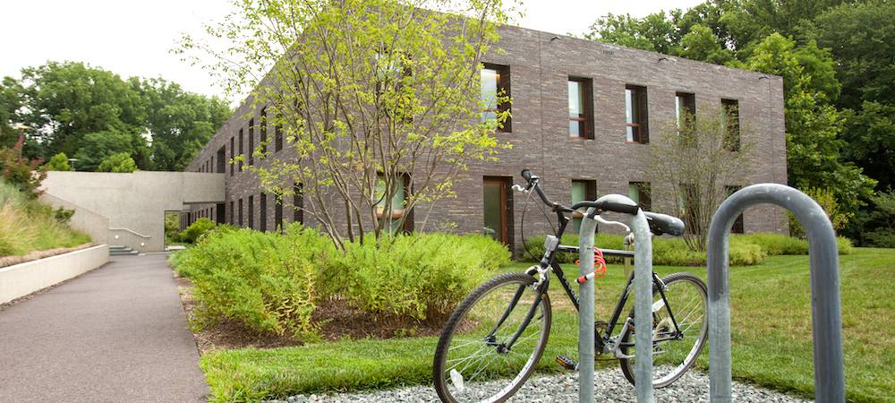 A bicycle leans against a bike rack in front of Kim Hall