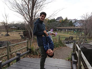 A young man stands on a bridge holding an upside-down laughing Japanese boy