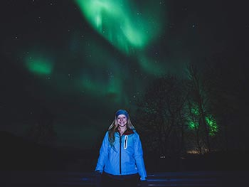 A young woman smiles in the foreground with the aurora borealis in the background