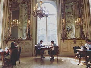 Two young men study at an ornate table in elaborate neo-baroque surroundings