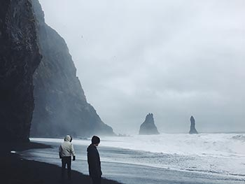 Two figures bundled in winter coats wander a black sand beach with the ocean roaring in the background