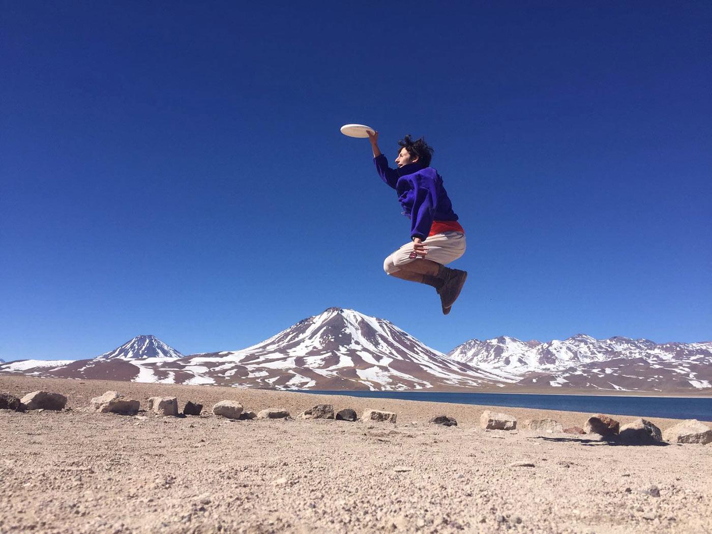 Man jumping in the air catching a frisbee with mountains in the background.