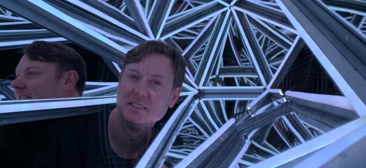 Reflections of Justin Geller within a mirrored structure