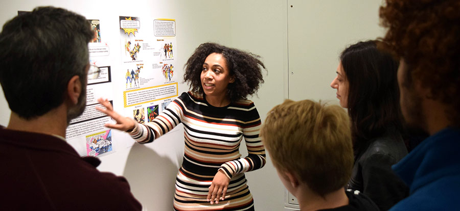 A student shows their work during a gallery talk