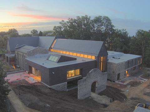 Exterior of the library under construction at sunrise.