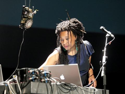 Pamela Z performing behind a laptop and microphones