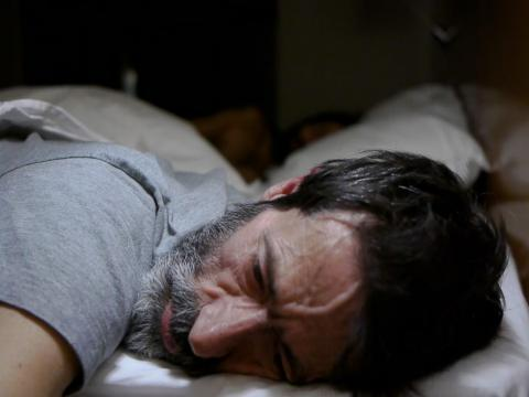 A bearded man lying on his stomach in bed appearing distressed