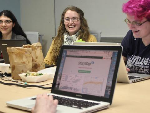 a group of student workers at a table, working at laptops and eating lunch