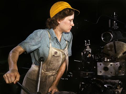 A woman operating a lathe