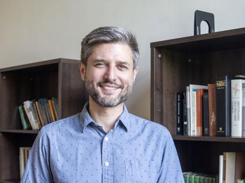 Matthew Farmer stands near his bookcase in his office