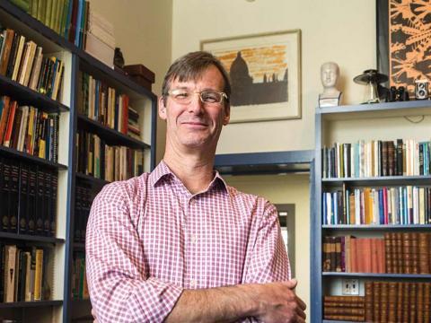 Associate Professor of History Darin Hayton stands in his office