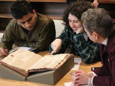students and a faculty member looking at a rare book from Quaker and Special Collections