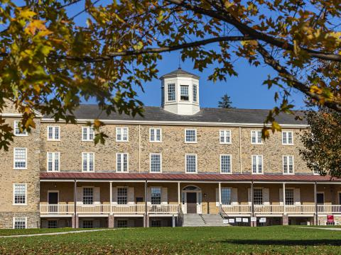 Wide shot of Founders Hall and Green framed by fall foliage