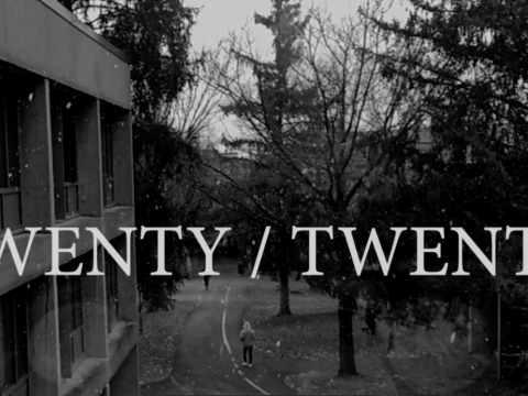 "A black-and-white photo taken from a second story window of campus as it is snowing with the words ""Twenty/Twenty"" written on top of them"