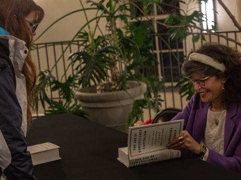 "Shoshana Zuboff signs a student's copy of her book, ""Surveillance Capitalism"" at an event at Haverford College"