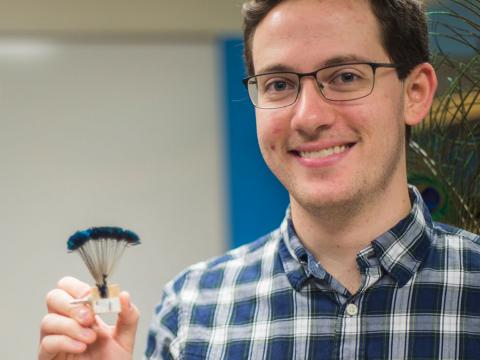 Suzanne Amador Kane and Daniel Van Beveren pose with one of their robotic feathers from their experiment.