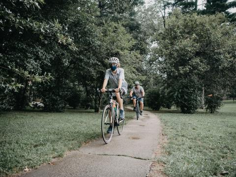Matthew Katz '22 wearing a helmet and mask bikes part of the Main Line Greenway