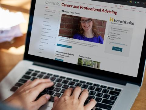 A laptop screen, viewed over the shoulder of an unseen student, showing the homepage for the Center for Career and Professional Advising