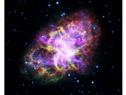 A brilliant ball of purple, green, and yellow light that is the Crab Nebula, shown as X-ray, ultraviolet, infrared, and visible light