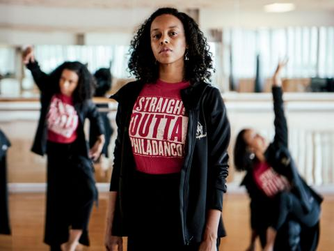 "Dana Nichols, wearing a ""Straight Outta Philadanco"" tshirt, stands in a dance studio with dancers and a mirror behind her."