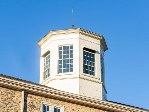 The sun shines on Founders Hall's cupola against a blue sky