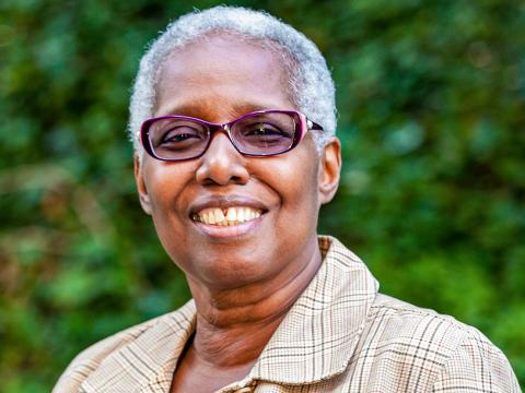 A headshot of Joyce Bylander, wearing purple glasses and a plaid jacket