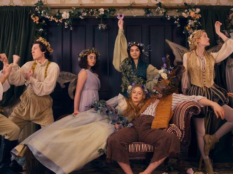 """The cast of Dickinson in period costume, draped in flowers, during an onscreen performance of """"A Midsummer Night's Dream"""" with one of the actors in a donkey mask"""