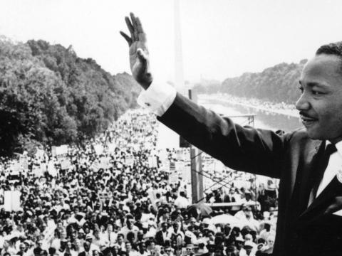 Martin Luther King, Jr. with his hand raised speaking to the crowd on the Mall during the March on Washington.