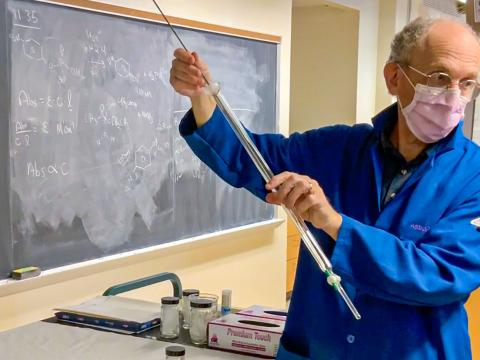 Instructor Mark Stein wears a mask while conducting a chemistry experiment for a video camera.