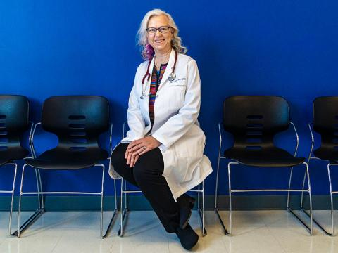 Dr. Yngvild Olden seated in her white lab coat