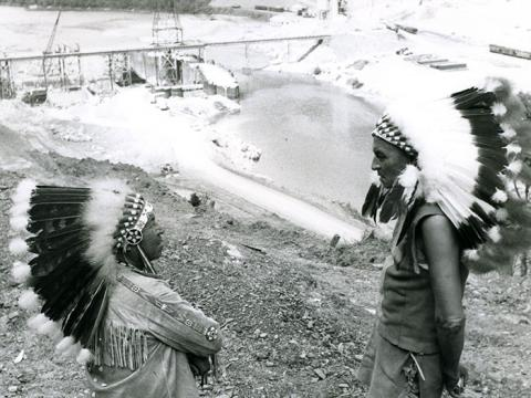 Harry Watt and Abner Jimeson are shown in Plains Indian-style war bonnets and dress with the Kinzua Dam under construction in the background