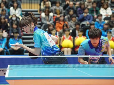 A couple with fierce expressions poised to play table tennis