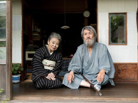 An elderly couple wearing traditional Japanese clothing sit together on a porch