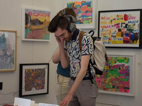 Students wear headphones and interact with an exhibit
