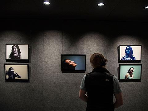 A wall with TVs showing various women