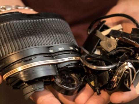 hands cradle a broken camera