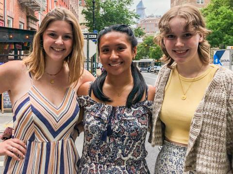 Eleanor, Kayla, and Madeline are dressed in nice clothes standing on a New York street.