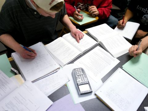 papers and a calculator scattered across a table where students work