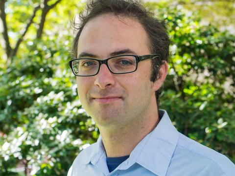 Professor Daniel Grin stands in front of greenery wearing a blue button down shirt.