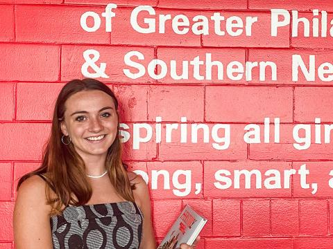 """A picture of Fiona in front of a pink wall with the words """"of Great Philadelphia & Southern New Jersey inspiring all girls to be strong, smart, and bold."""""""