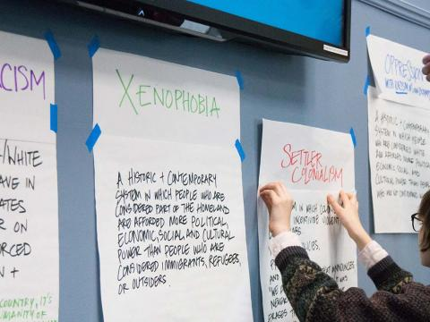 students place notes about social justice issues on a wall