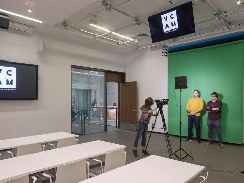 A student films in the VCAM using a green screen