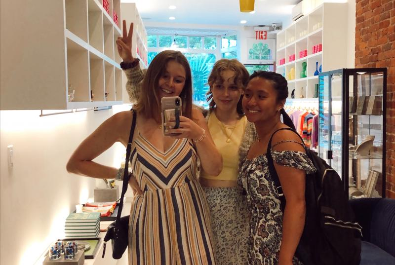 The Haute team takes a photo in a full-length mirror in a New York fashion store.