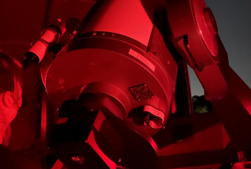 A red lit photo of someone looking through a large telescope.