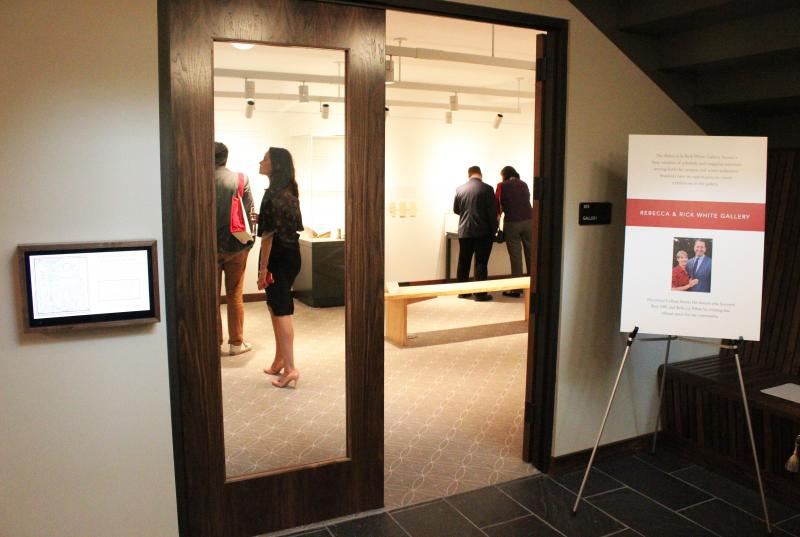 Photograph of the entrance to the Rebecca and Rick White Gallery in Lutnick Library; the door is open, and several people are inside looking at items on exhibit.