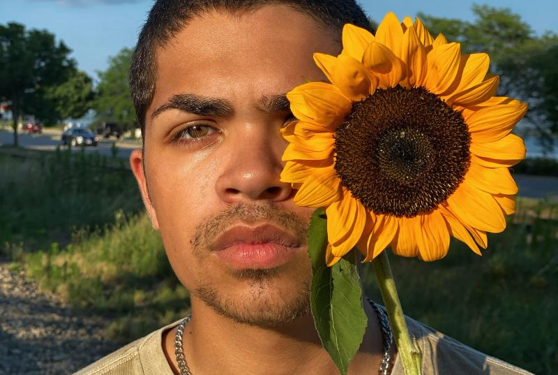 Kevin holds a large, yellow sunflower in front of his left eye