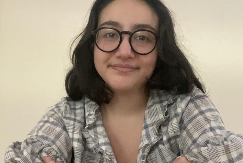 Monica wears glasses and a plaid button-down shirt and sits with her arms crossed