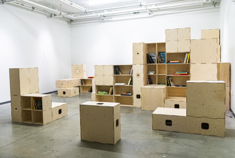 "The modular ""boxel"" showcased in an exhibit as bookshelves, platforms, seats, and desks"