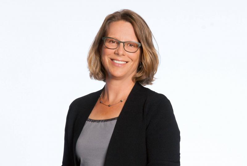 A portrait of Clair Colburn '91, wearing glasses and a black blazer